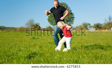 Girl an her Dad playing soccer