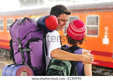 girl and a boy travelling with  backpacks-at a train station - stock photo