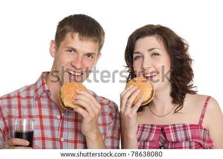 Girl and a guy eating cheeseburgers and drinking a refreshing drink. - stock photo
