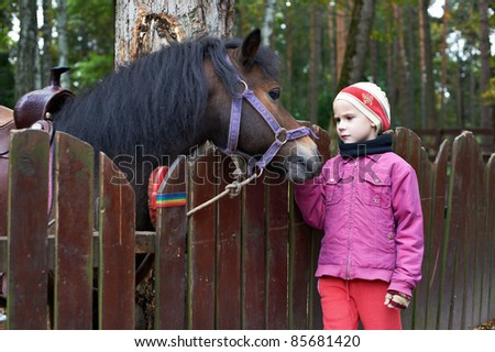 Girl and a little horse pony near corral