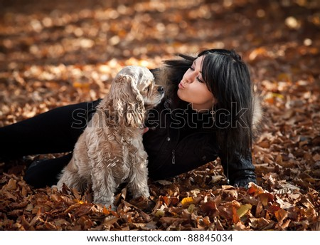 Girl and american cocker spaniel in the autumn forest