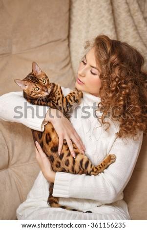Girl and Bengal cat home. Home comfort. Girl hugging cat. - stock photo
