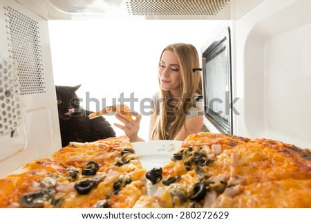 Girl and black cat looking at a pizza in the microwave - stock photo