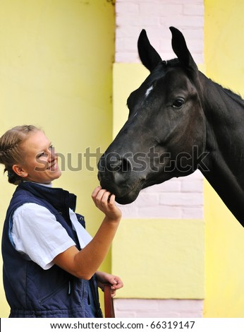 Girl and black sportive horse before competitions - stock photo