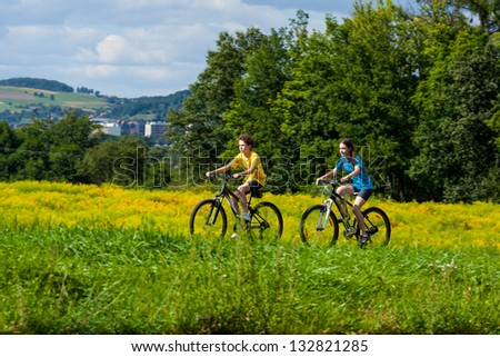 Girl and boy biking - stock photo
