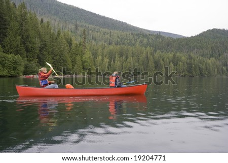 Girl and boy canoeing in Canada - stock photo