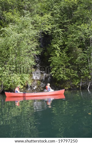 Girl and boy canoeing looking at a waterfall, Canada - stock photo