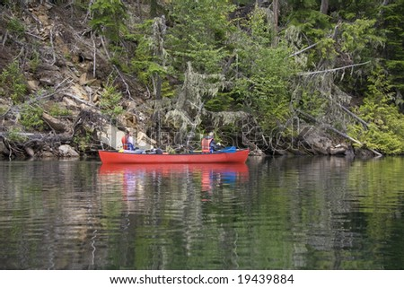 Girl and boy canoeing near the shore in Canada - stock photo