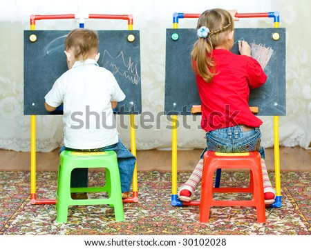 girl and boy drawing on the blackboard with chalk - stock photo