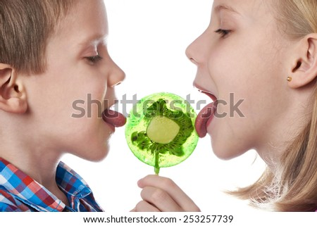 Girl and boy eating a lollipops isolated - stock photo