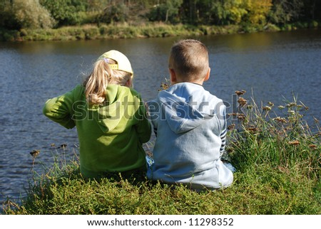 Girl and boy fishing on the river - stock photo