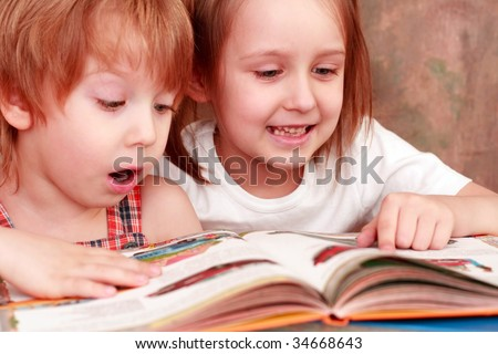 girl and boy friendly reading an interesting book - stock photo