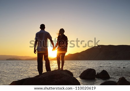 Girl and boy holding hands and watching the sun by the sea - stock photo