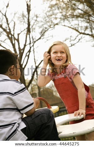 Girl and boy outside playing on playground. Vertically framed shot. - stock photo