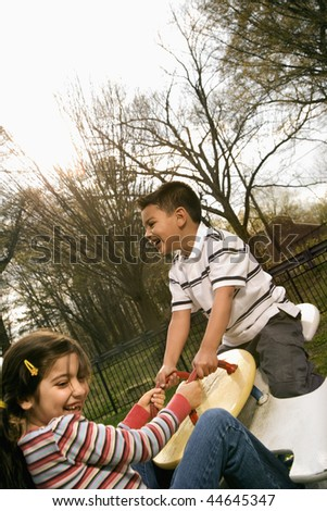 Girl and boy outside playing on seesaw. Vertically framed shot. - stock photo