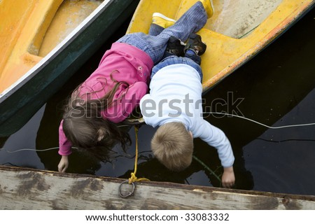 girl and boy playing in yellow boat - stock photo