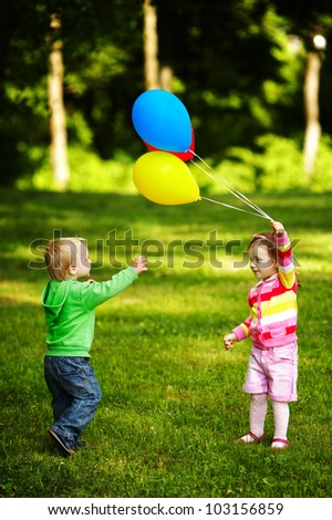 girl and boy playing with balloons in park - stock photo