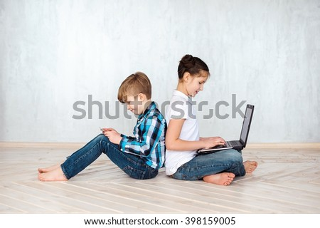 Girl and boy playing with gadgets - laptop and tablet - stock photo