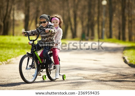 girl and boy riding on bicycle - stock photo