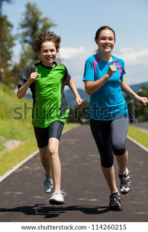 Girl and boy running, jumping outdoor - stock photo