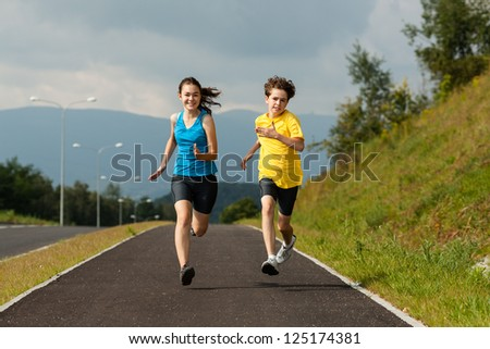 Girl and boy running outdoor - stock photo