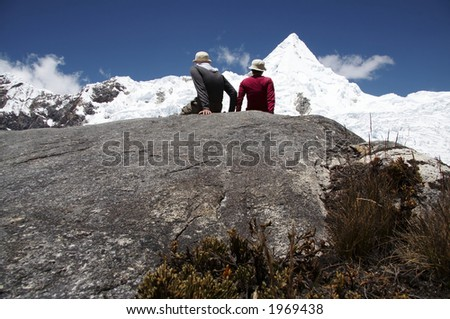 Girl and boy setting on the stone in high mountain - stock photo
