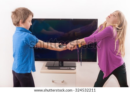 Girl and boy siblings fighting over the remote control in front of the TV - stock photo