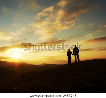 Girl and boy silhouette on the sunset background - stock photo