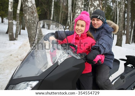 Girl and boy sitting behind the wheel of a snowmobile in the forest - stock photo