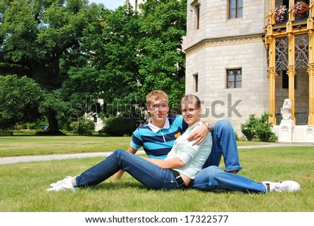 girl and boy sitting on grass
