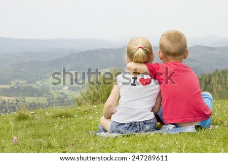 girl and boy sitting on the mountain in an embrace and look at the horizon - stock photo