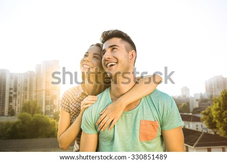 Girl and boy sitting outdoors at roof. They cheerfully smiling and enjoying good weather. Nice city panorama - stock photo