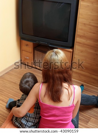 Girl and boy sitting watching television - stock photo