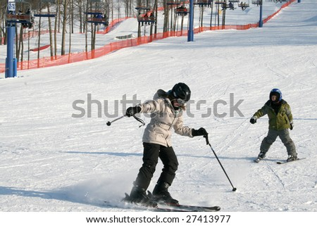 Girl And Boy Skiing Downhill