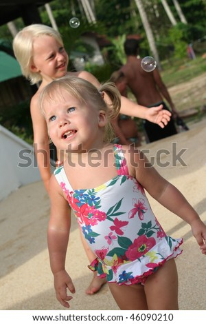 Girl and boy standing near swimmig pool - stock photo