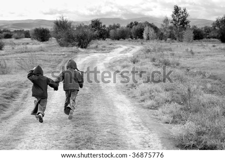 girl and boy standing or running on the road - stock photo
