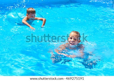 Girl and boy swimming into a resort pool