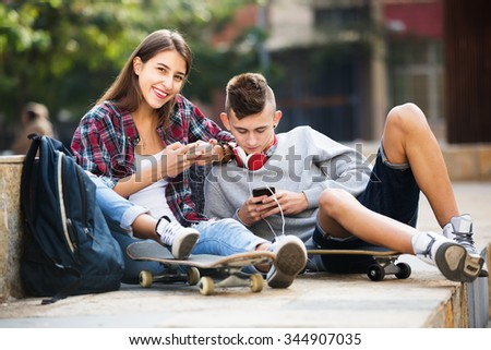 Girl and boy teens playing on mobile phones and listening to music - stock photo