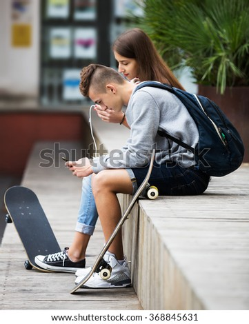 Girl and boy teens playing on smartphones and listening to music outdoors - stock photo