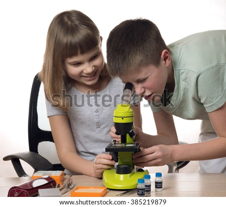 girl and boy teens with microscope isolated on white background - stock photo