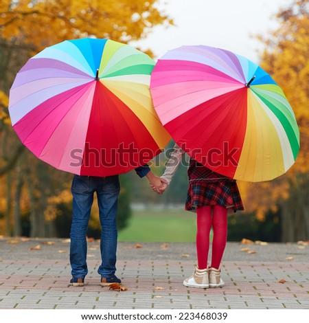 girl and boy under bright colored umbrellas - stock photo