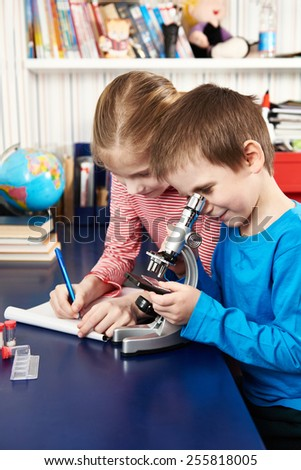 Girl and boy uses a microscope and writes results at home learning table - stock photo
