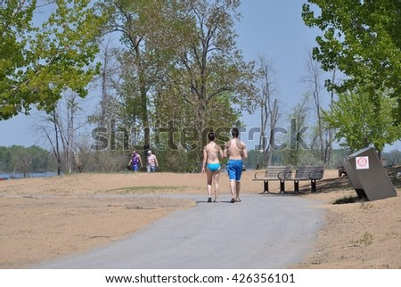 Girl and boy walking in beach road wearing swimwear only - stock photo