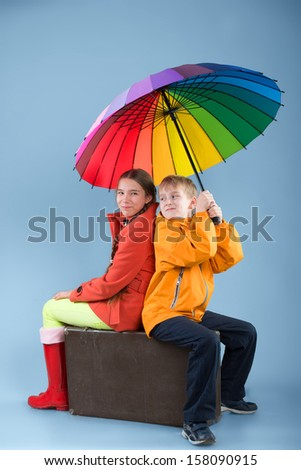 Girl and boy with a colorful umbrella sitting on an old traveling bag  - stock photo