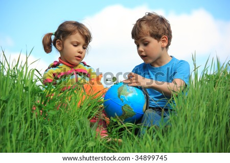 girl and boy with globe on meadow - stock photo