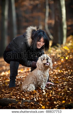 Girl and cocker spaniel in the autumn forest.