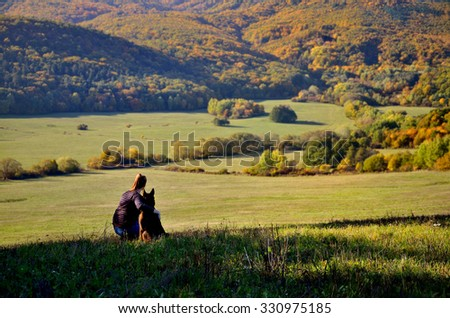 Girl and dog are sitting over wonderful autumn landscape full of colored trees and calm forest - stock photo