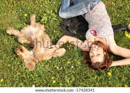 girl and dog lying in the grass - stock photo