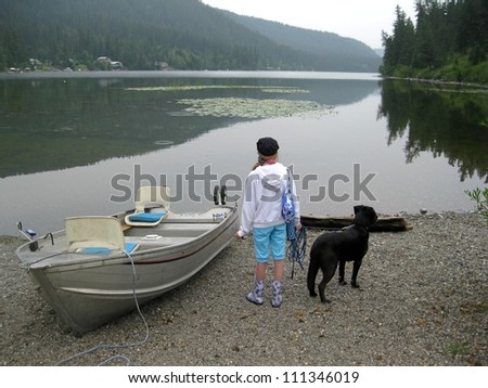 Girl and dog ready to go boating. - stock photo