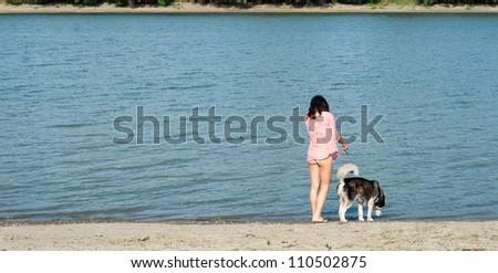 girl and dog walking along the coast - stock photo